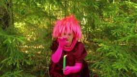Młoda guślarka siedzi w lesie i wykonuje rytuał z świeczką zdjęcie wideo