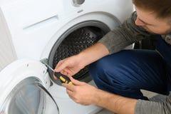 Młoda hydraulika naprawiania pralka obraz royalty free