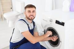 Młoda hydraulika naprawiania pralka zdjęcia stock