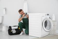 Młoda hydraulika naprawiania pralka fotografia royalty free