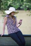 Młoda i ładna kobieta czyta wiadomość na jej smartphone zdjęcie stock