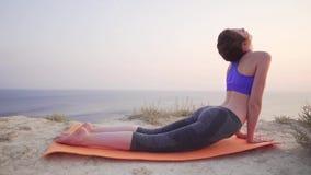 Młoda i atrakcyjna dziewczyna robi rozciąganiu z dennym widokiem w tle Relaksujący i skupiający się kobiety ćwiczy joga zbiory