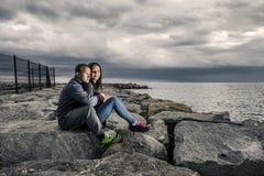 Młoda i atrakcyjna para siedzi na molu robić kamienie Obraz Stock