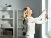 Młoda i piękna blond kobieta otwiera okno zdjęcia stock