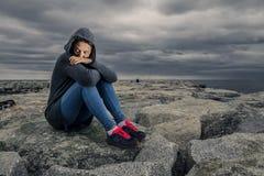 Młoda i piękna kobieta w popielatym długim pulowerze siedzi na gramocząsteczce Zdjęcia Royalty Free