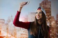 Młoda i pozytywna dziewczyna fotografuje na jej smartphone w jej pokoju na tle miasto przedstawiający na Zdjęcia Royalty Free