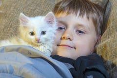 Młoda i rozochocona chłopiec z białym kotem ogląda kamerę na leżance obrazy stock