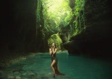 Młoda i seksowna boginka chodzi w jarze zostawać w słońc światłach bawić się z turkus wodą wearig długi fotografia stock