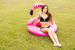 Młoda i seksowna dziewczyna ma zabawę, śmia się zabawę na trawie i ma blisko basenu na nadmuchiwanym różowym flamingu w kąpaniu Zdjęcia Royalty Free