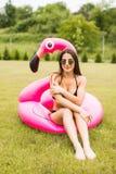 Młoda i seksowna dziewczyna ma zabawę, śmia się zabawę na trawie i ma blisko basenu na nadmuchiwanym różowym flamingu w kąpaniu Obraz Stock