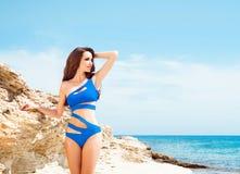 Młoda i seksowna kobieta pozuje w błękitnym swimsuit na plaży Zdjęcia Royalty Free
