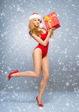 Młoda i seksowna Santa dziewczyna w czerwonym swimsuit na śnieżnym tle Fotografia Stock