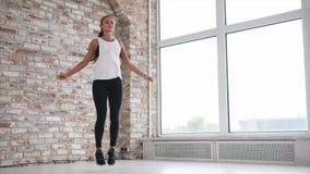 Młoda i sportowa kobieta grże up mięśnie skokową arkaną w sprawność fizyczna klubie zdjęcie wideo