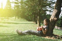Młoda i szczęśliwa azjatykcia dziewczyna bawić się z ukelele gitarą przy parkiem w pogodnym ranku obraz stock
