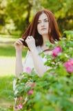 Młoda imbirowa kobieta dotyka jej włosianego lato portret Obraz Stock