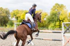 Młoda jeździec dziewczyna skacze nad barier na jej kursie Zdjęcia Royalty Free