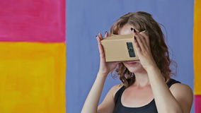 Młoda kędzierzawa kobieta używa rzeczywistość wirtualna szkła Google karton zbiory