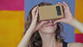 Młoda kędzierzawa kobieta używa rzeczywistość wirtualna szkła Google karton zbiory wideo