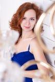Młoda kędzierzawa miedzianowłosa kobieta w błękit sukni Zdjęcie Royalty Free