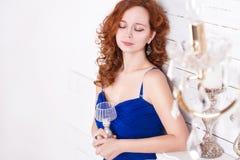 Młoda kędzierzawa miedzianowłosa kobieta w błękit sukni Fotografia Royalty Free
