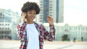 Młoda kędzierzawa z włosami kobieta słucha muzyka w hełmofonach i śpiewackiej piosence zbiory