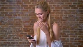 Młoda Kaukaska blond dziewczyna używa smartphone, śmiechy, ściana z cegieł w tle