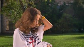 Młoda Kaukaska brunetki dziewczyna siedzi w parku na trawie i słucha muzyka na hełmofonach na smartphone, marzy zbiory