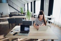 Młoda Kaukaska kobieta uśmiecha się laptop i używa w kawiarni Tam ` s inny laptop, telefon i filiżanka kawy niedaleka, Zdjęcia Royalty Free