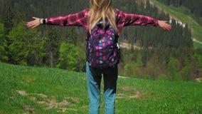 Młoda Kaukaska kobieta z plecakiem i okularów przeciwsłonecznych stojakami na górze góry i podnosi ona ręki przeciw jako tła popa zbiory wideo