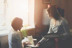 Młoda kelnerka w fartuch porci kawy latte zdjęcia royalty free