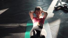 Młoda kobieta ćwiczy abdominals w gym w sportswear atrakcyjna dziewczyny atleta angażował w ćwiczeniach na pracie brzusznej zdjęcie wideo