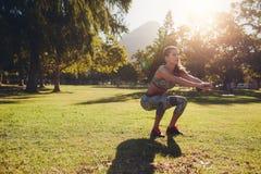 Młoda kobieta ćwiczy w parku na ładnym letnim dniu Zdjęcie Royalty Free
