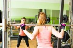 Młoda kobieta ćwiczy z barbell w gym obraz stock