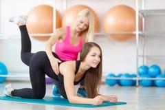 Młoda kobieta ćwiczy z jej sprawność fizyczna instruktorem fotografia royalty free