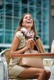 Młoda kobieta śmia się przy wiadomością tekstową Zdjęcia Stock