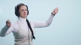 Młoda kobieta śpiew przy hełmofonami na białym tle i taniec zbiory wideo