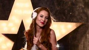 Młoda kobieta śpiewa piosenkę z a w hełmofonach zdjęcie wideo