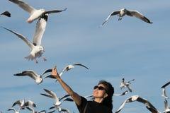 Młoda kobieta żywieniowi ptaki ręką Fotografia Stock