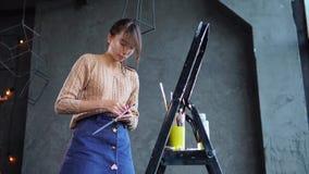 Młoda kobieta artysta gniesie out farbę od tubas paleta w warsztacie zbiory wideo