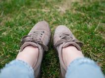 Młoda kobieta, będący ubranym w niebieskich dżinsach i sneakers siedzi na zielonej trawie, zamyka w górę zdjęcia royalty free