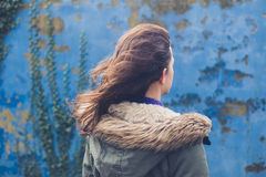 Młoda kobieta błękit ścianą na wietrznym dniu zdjęcia stock