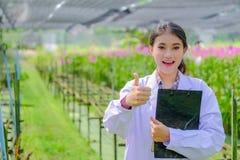 Młoda kobieta badacz w białej sukni, aprobaty i bada ogród przed zasadzać nowej orchidei zdjęcia stock