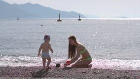 Młoda kobieta bawiąca się z synem na plaży przy morzu w zwolnionym tempie zbiory
