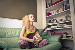 Młoda kobieta bawić się gitarę Obrazy Royalty Free