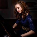 Młoda kobieta bawić się uroczystego pianino Obraz Royalty Free