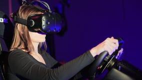 Młoda kobieta bawić się w samochód przejażdżki symulancie przy VR klubem, używać nowożytną rzeczywistości wirtualnej słuchawki Wi zbiory
