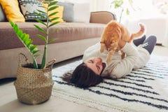 M?oda kobieta bawi? si? z kotem na dywanie w domu Mistrzowski lying on the beach na pod?odze z jej zwierz?ciem domowym fotografia royalty free