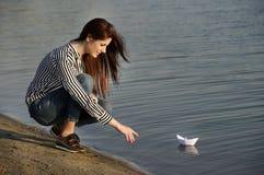 Młoda kobieta bawić się z papierową łodzią Obraz Stock
