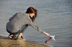 Młoda kobieta bawić się z papierową łodzią Obraz Royalty Free