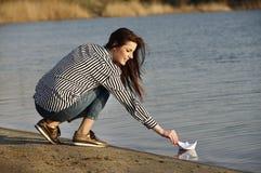 Młoda kobieta bawić się z papierową łodzią Obrazy Stock